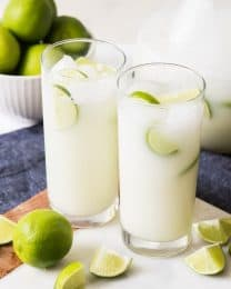two glass cups full of brazillian limade and ice with limes and lime wedges around them