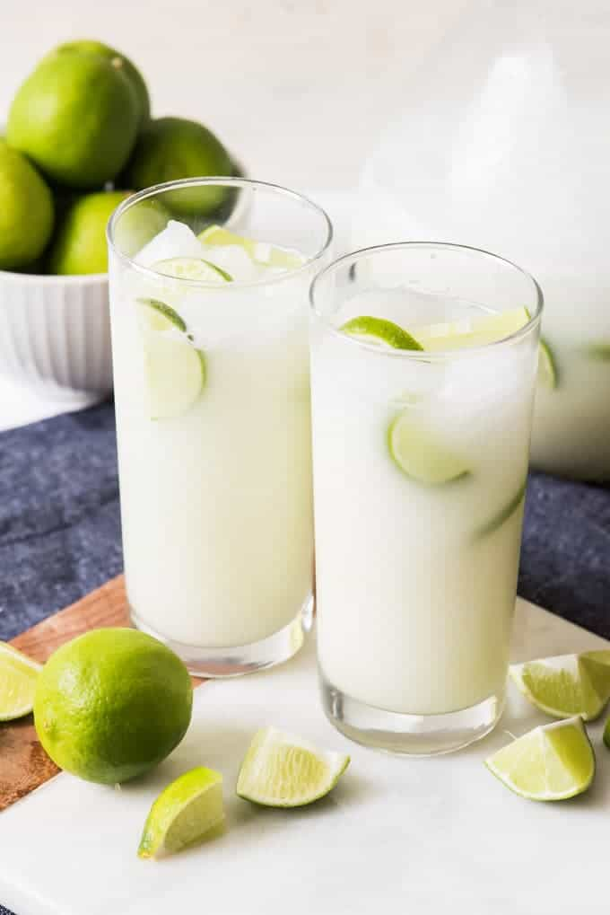 Two glasses of Brazilian Lemonade (also known as Swiss Lemonade or Brazilian Limeade), with ice cubes and lime wedges sitting on a cutting board with sliced limes.