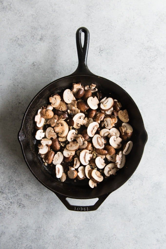 Mushrooms in a cast iron skillet for a cheesy tortellini & chicken pumpkin alfredo bake with mushrooms.