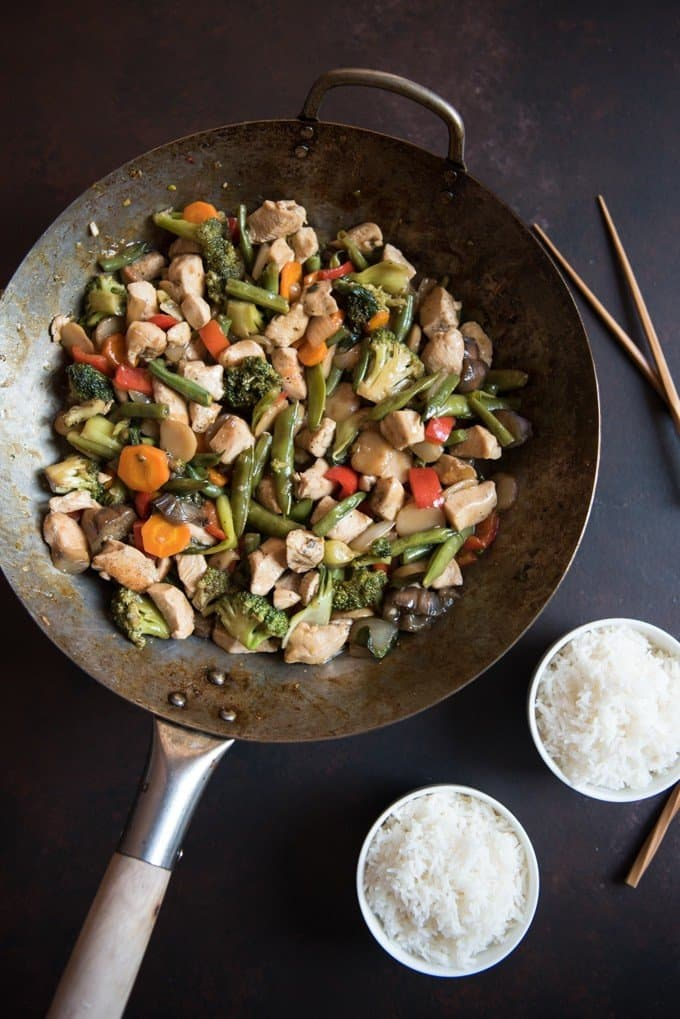 Large wok with a stir-fry made from chicken, carrots, green beans, broccoli, peppers, and mushrooms in a brown sauce.