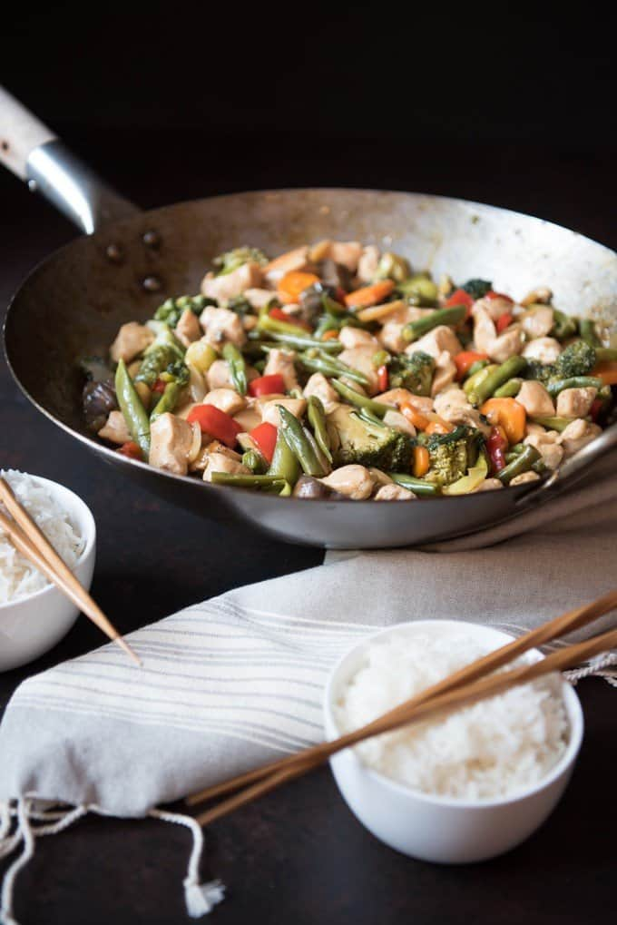 Large wok filled with vegetables and chicken in a classic, easy stir-fry dish.