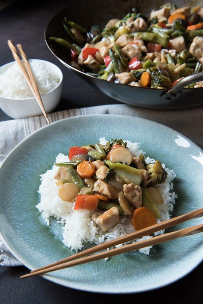 A plate of easy chicken & vegetable stir-fry served over white rice with chopsticks as utensils.