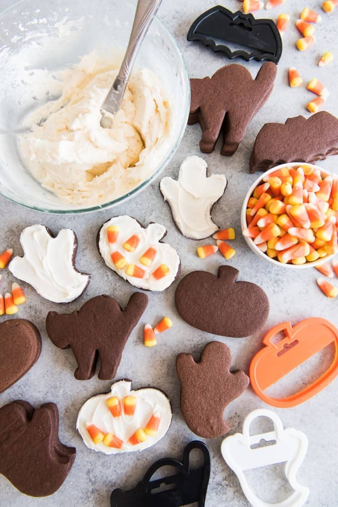 Chocolate rolled sugar cookies cut out in Halloween shapes of cats, ghost and pumpkins.