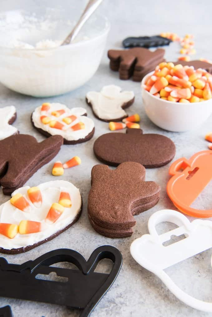 Bowls of candy corn and frosting used to decorate Halloween chocolate cut out sugar cookies.