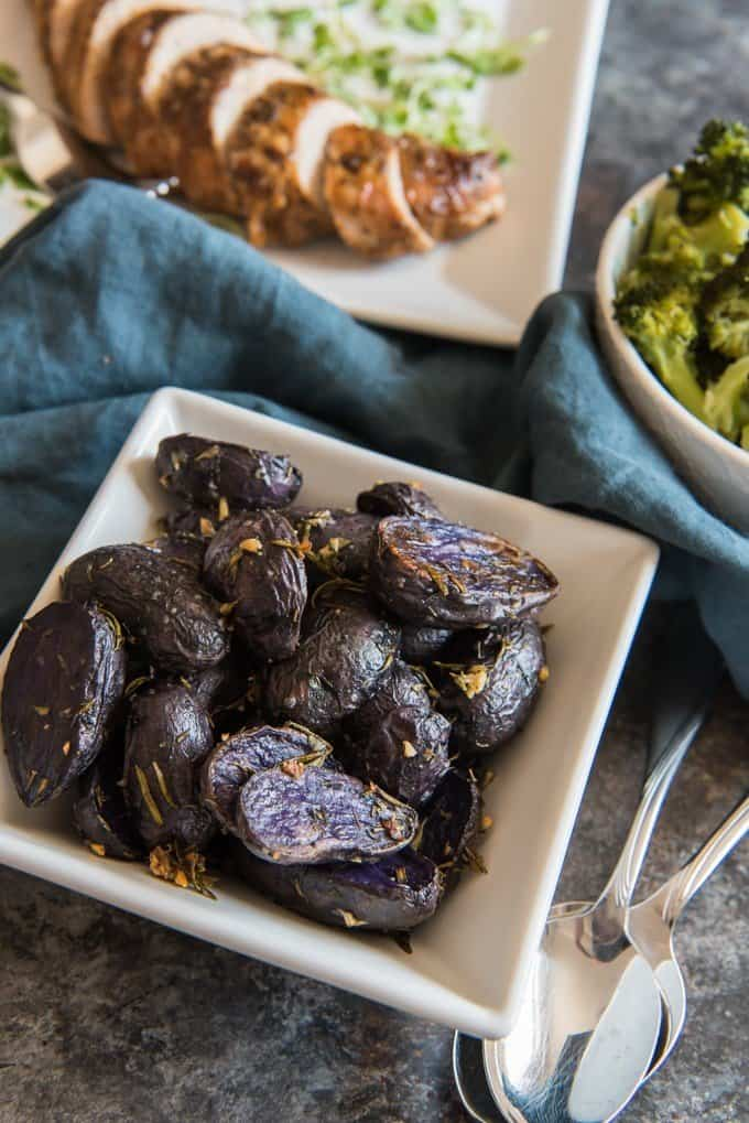 The Roasted Baby Purple Potatoes are tossed with rosemary, thyme, and garlic and served in a square shaped bowl.