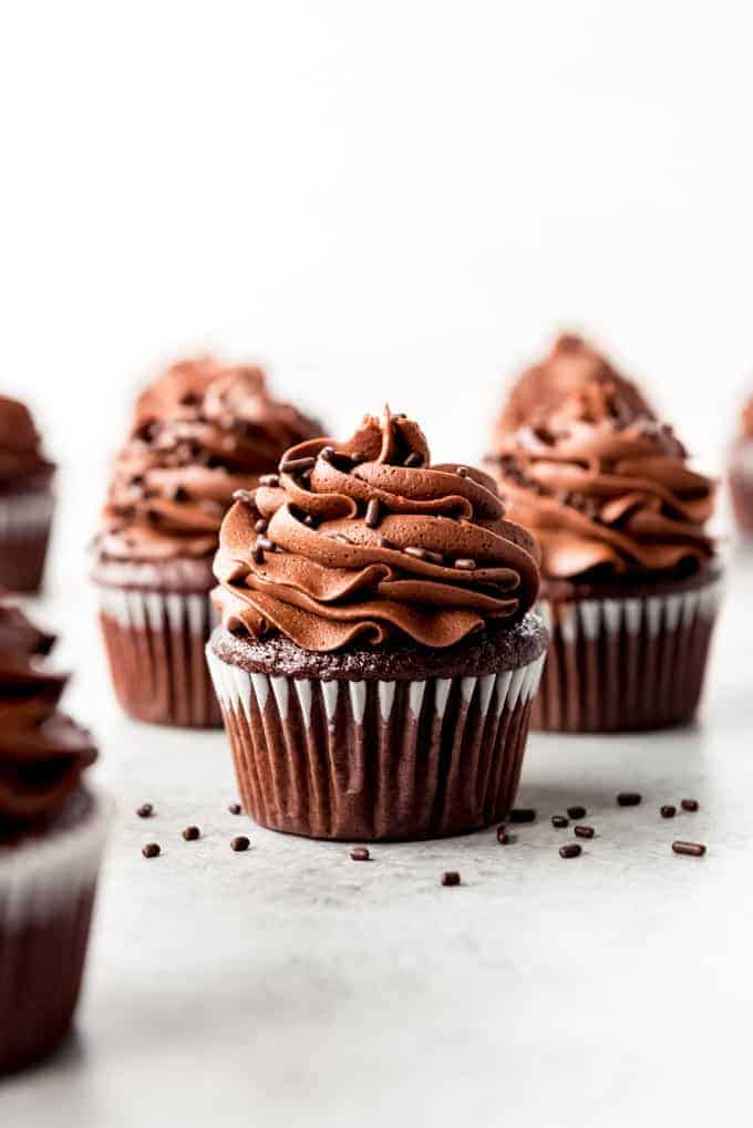 An image of homemade chocolate cupcakes with chocolate frosting and sprinkles on top.