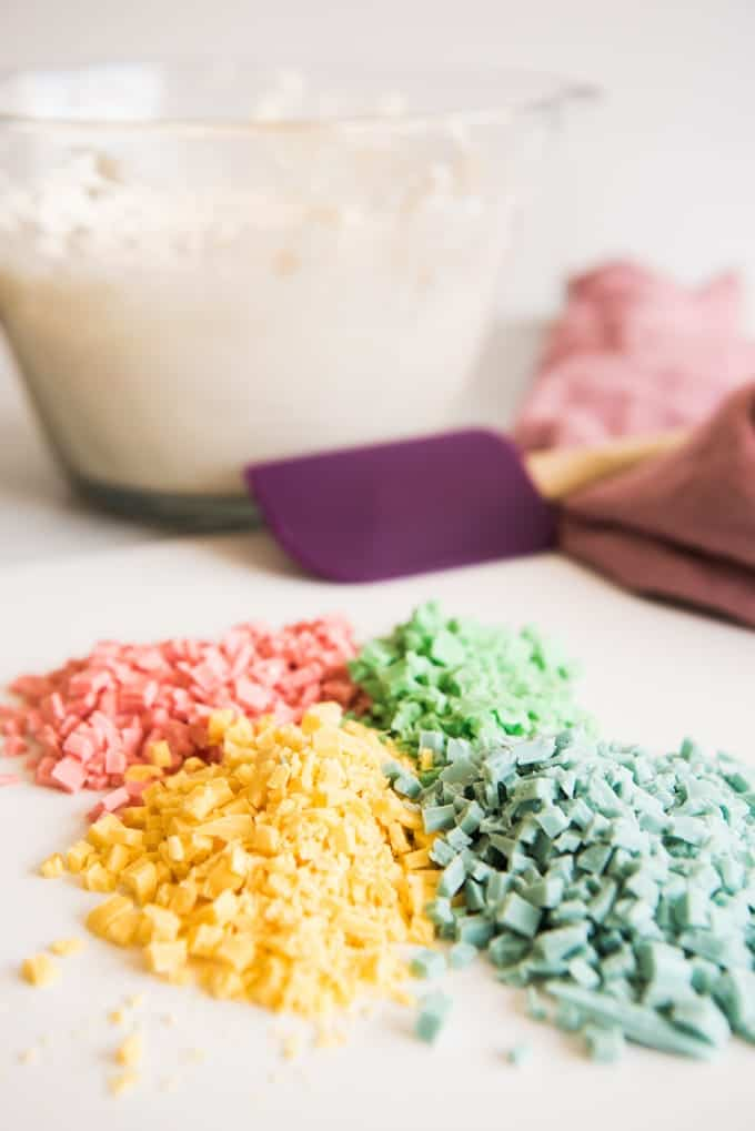 Colorful pastel rainbow chips in piles to be stirred into a vanilla cream cheese frosting base to make rainbow chip frosting.