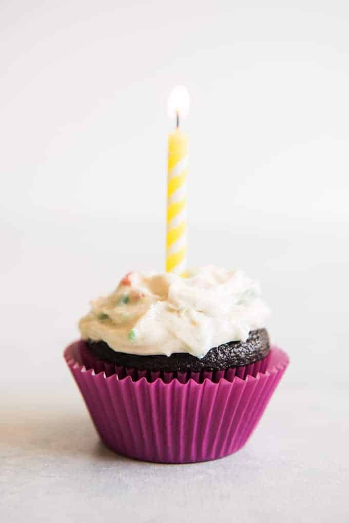 Chocolate cupcake with homemade rainbow chip frosting in a purple cupcake liner with a lit yellow birthday candle.