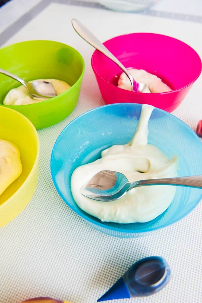 Colorful bowls with melted white chocolate and spoons for stirring food coloring into them.