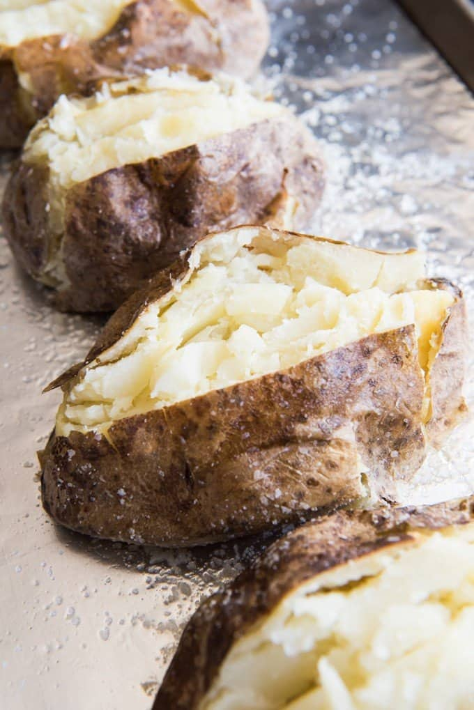 split open baked potatoes on baking sheet