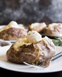 baked potatoes on plates with scooped balls of butter on top