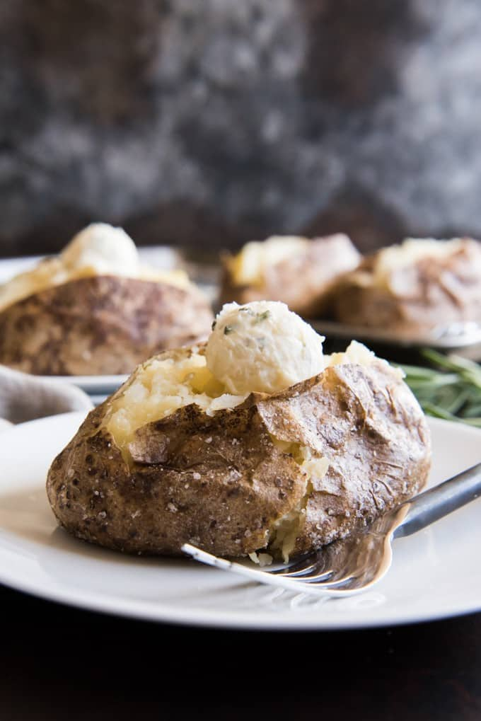 Baked potatoes might seem basic, but these Salt Crusted Baked Potatoes with Roasted Garlic & Rosemary Butter are anything but. These simple and easy steakhouse style russets get coated with olive oil and salt before baking, ensuring are a crispy, flavorful skin with tender, moist and fluffy insides! Naturally gluten-free and vegetarian-friendly, these are wonderful to serve if you have friends or family with dietary restrictions.