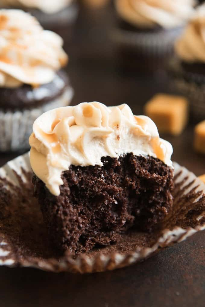 A chocolate cupcake with salted caramel frosting with a bite taken out of it.