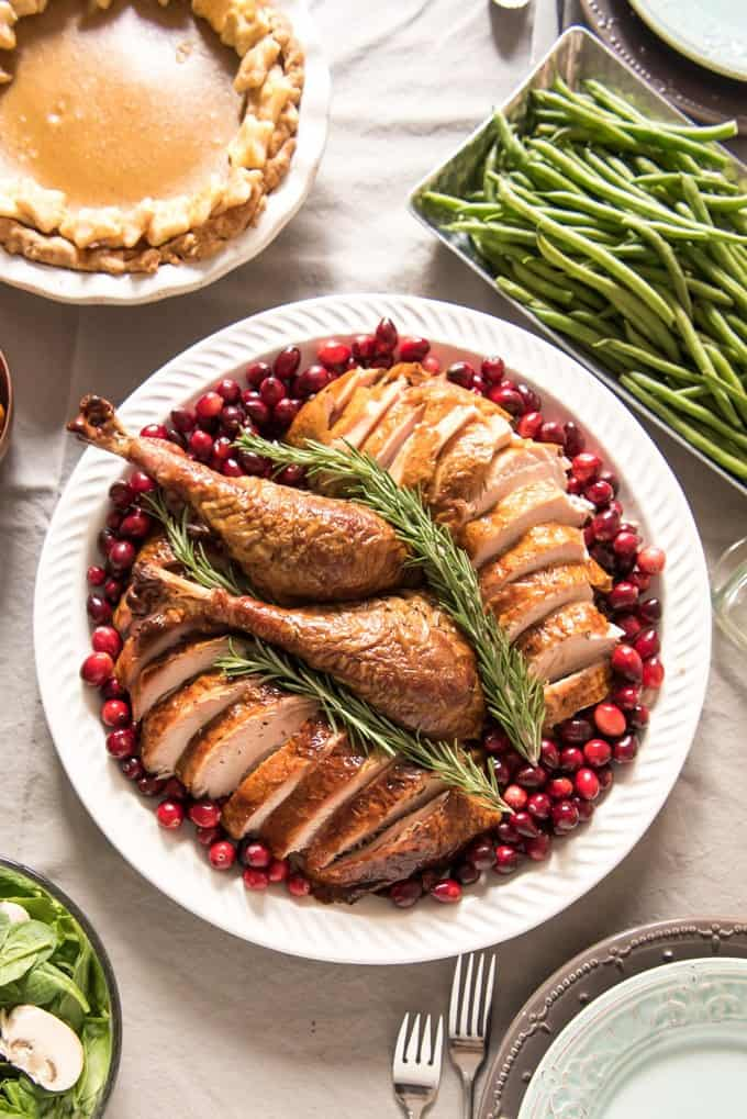 A smoked and brined turkey is a fanastic way to prepare your Thanksgiving bird for the traditional Thanksgiving Feast! This one is served sliced with whole fresh cranberries and sprigs of rosemary as a garnish.