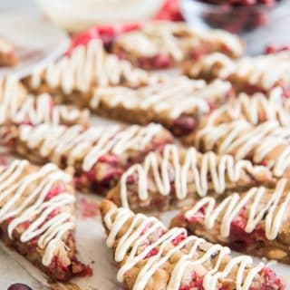 These festive and fun White Chocolate Cranberry Blondies are made with fresh cranberries, white chocolate chips, and chopped pecans, with a little extra melted white chocolate drizzled over the top for good measure!  A perfect addition to a holiday cookie platter at a Christmas cookie exchange party!