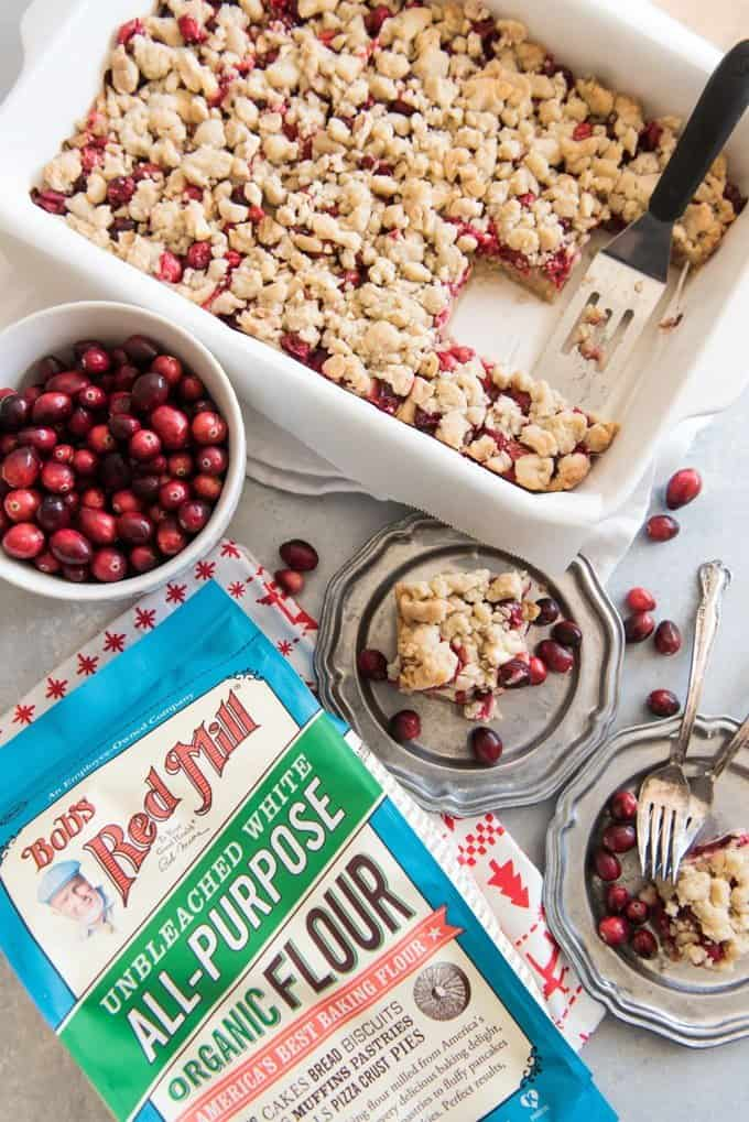 a white baking ddish full of cranberry shortcake bares with some pieces missing and a serving spatula resting inside. a bowl of fresh cranberries some plates with servings of cranberry shortcake and forks and a bag of bobs red mill to the side