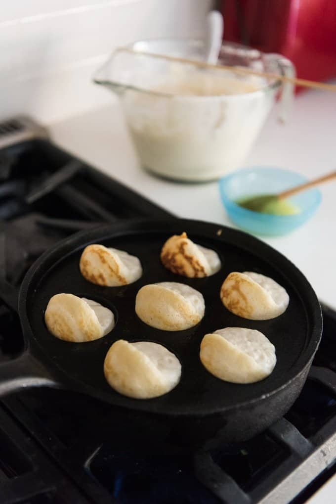 partially cooked aebleskivers in a cast iron pan on a stove