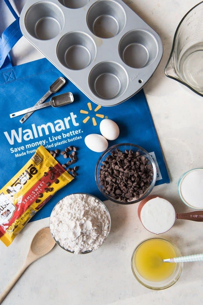 a muffin pan on top of a walmart reusable bag some measuring spons and ingredients needed to make chocolate chip muffins