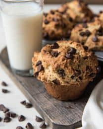 Chocolate chip muffins on a wooden board with a glass of milk and scattered chocolate chips around it