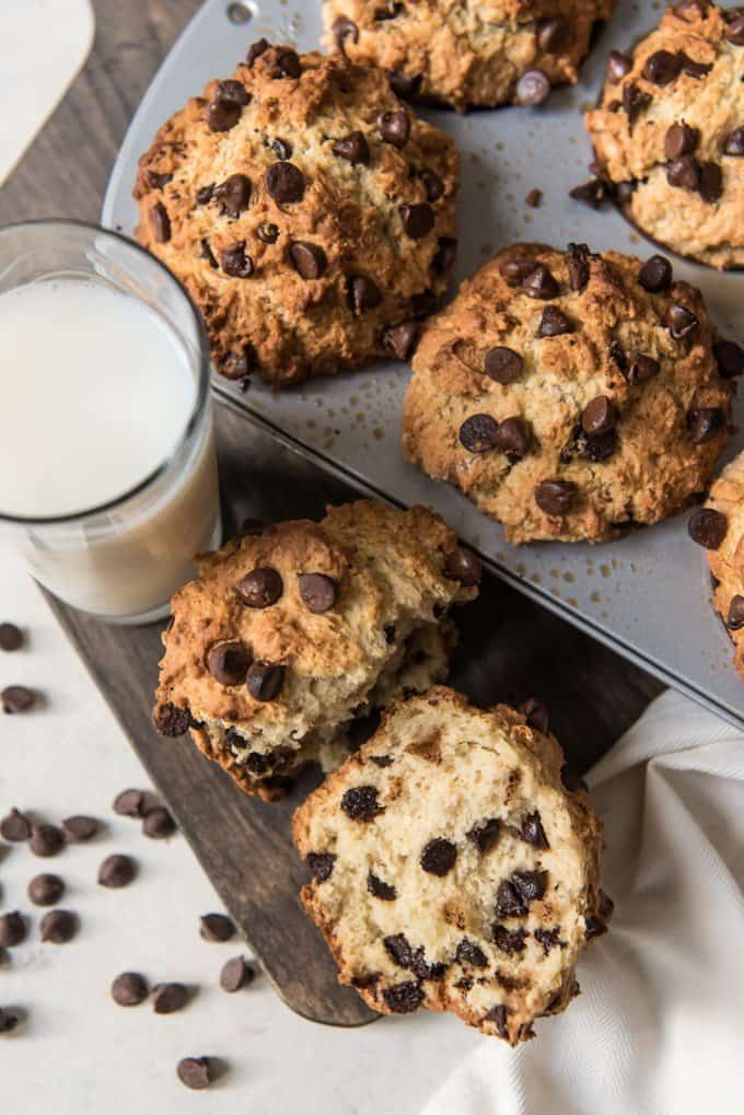 Chocolate chip muffins in a baking dish with one removed and split open beside it with a glass of milk and scattered chocolate chips