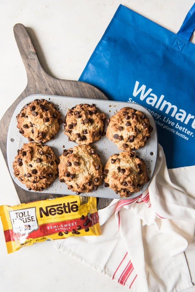 6 baked chocolate chip muffins in a an on a wooden cutting board next to a bag of chocolate chips white towel and walmart bag