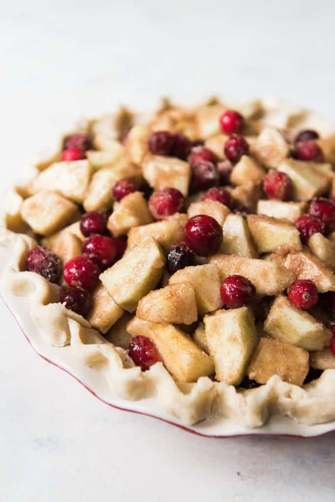 An unbaked pie crust filled with sliced apples, fresh cranberries, and cinnamon and sugar.