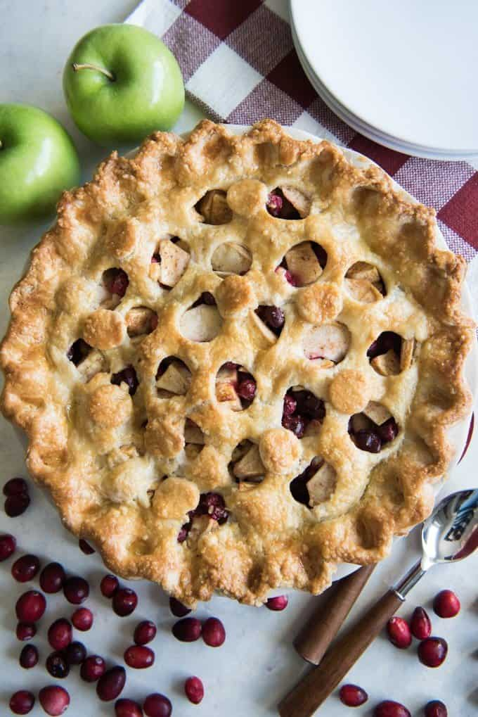 Cranberry Apple Pie is a sweet-tart and totally refreshing take on a classic apple pie and is a great addition to any Thanksgiving dessert table! The flaky, buttery crust, sweet apple pie filling, and tart bursts of fresh cranberries with just a hint of cinnamon make for a delicious and festive Fall dessert, sure to delight guests and family this holiday season.