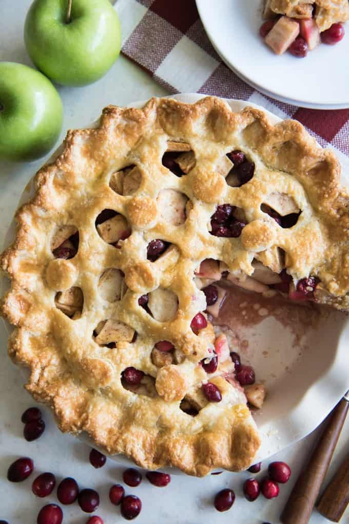 Apple Cranberry pie with a slice already taken out of it. Sweet, tart, and a refreshing change, perfect for a Thanksgiving or Christmas holiday dessert table.