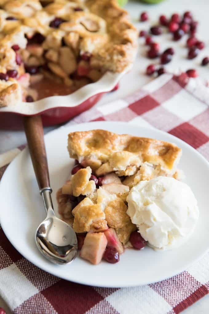 A slice of sweet-tart Cranberry Apple Pie served with a scoop of vanilla ice cream on the side.