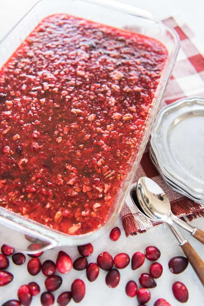 cranberry jello salad in baking dish with fresh cranberries spoons and plates to the sides
