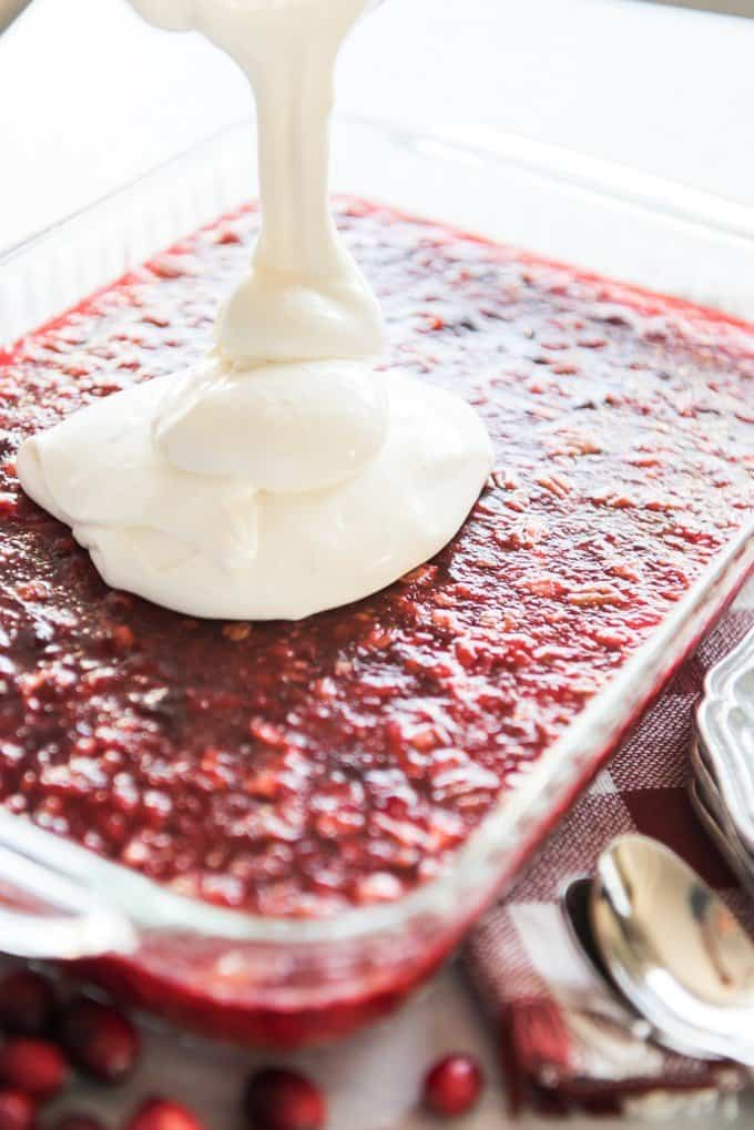 Pouring the tangy cream cheese and sour cream topping over a cranberry jello salad.