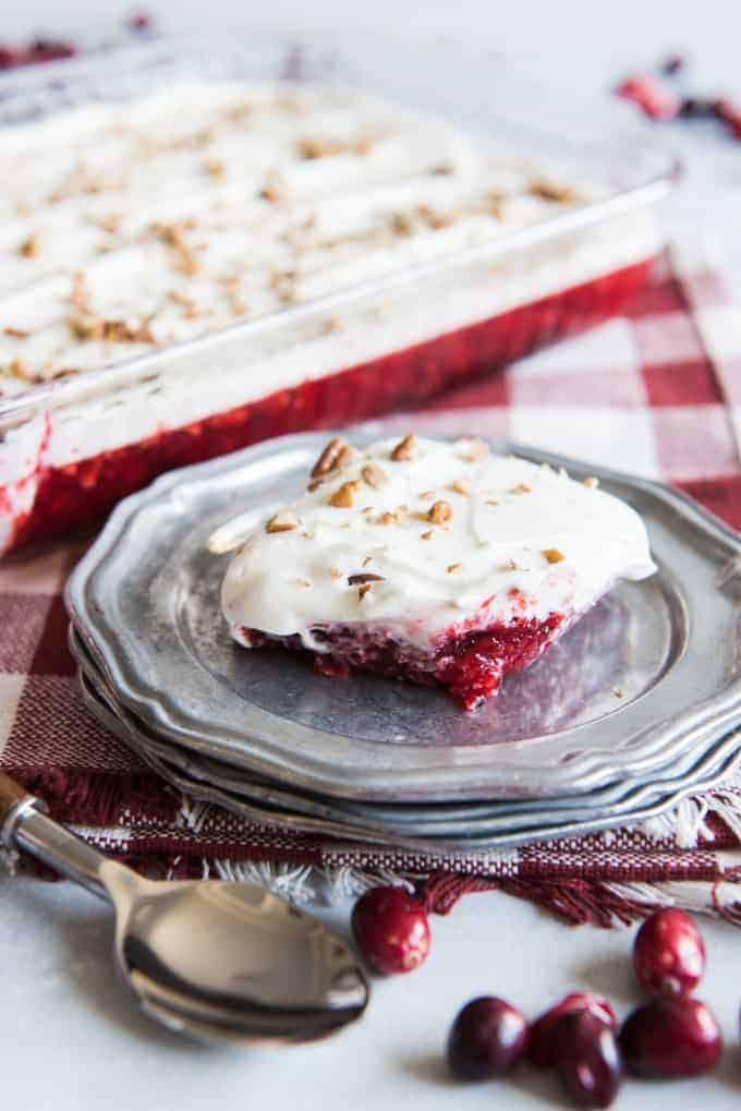Cranberry Jell-O Salad is a sweet-tart, dessert salad loaded with crushed pineapple, chopped pecans, cranberries and a tangy cream cheese topping!  It's perfect to serve for Thanksgiving dinner, Christmas dinner, or any night of the year!