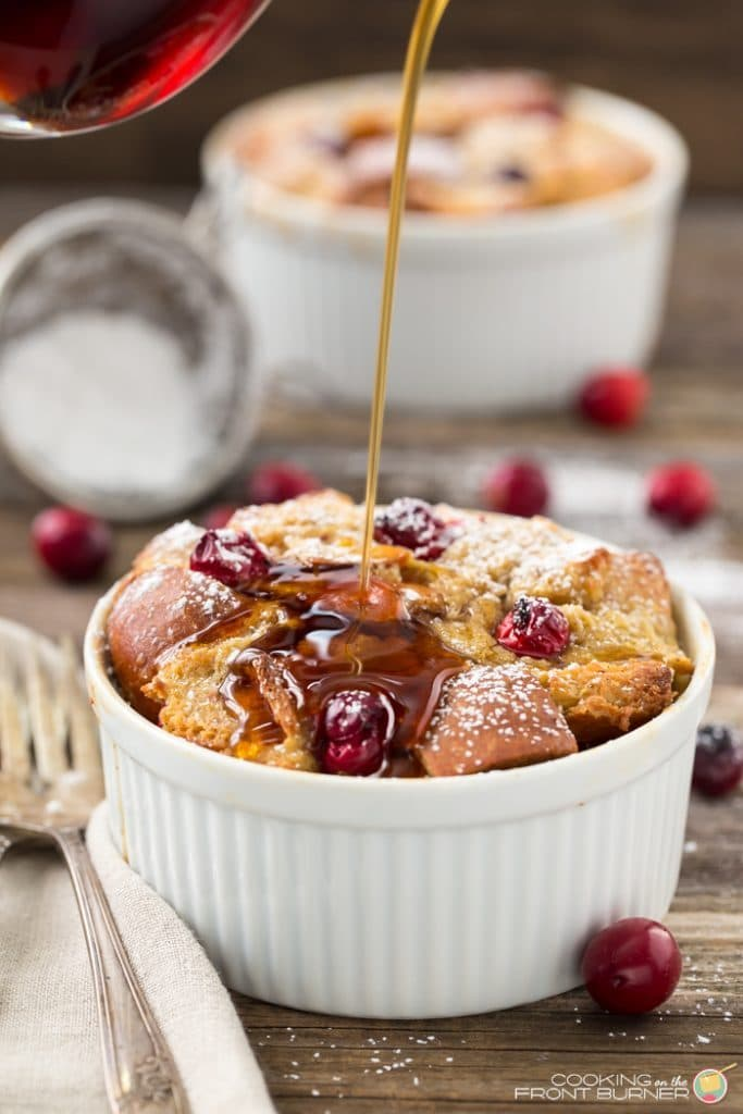 Cranberry french toast in a white ramekin with scattered berries around it and srup being drizzled on
