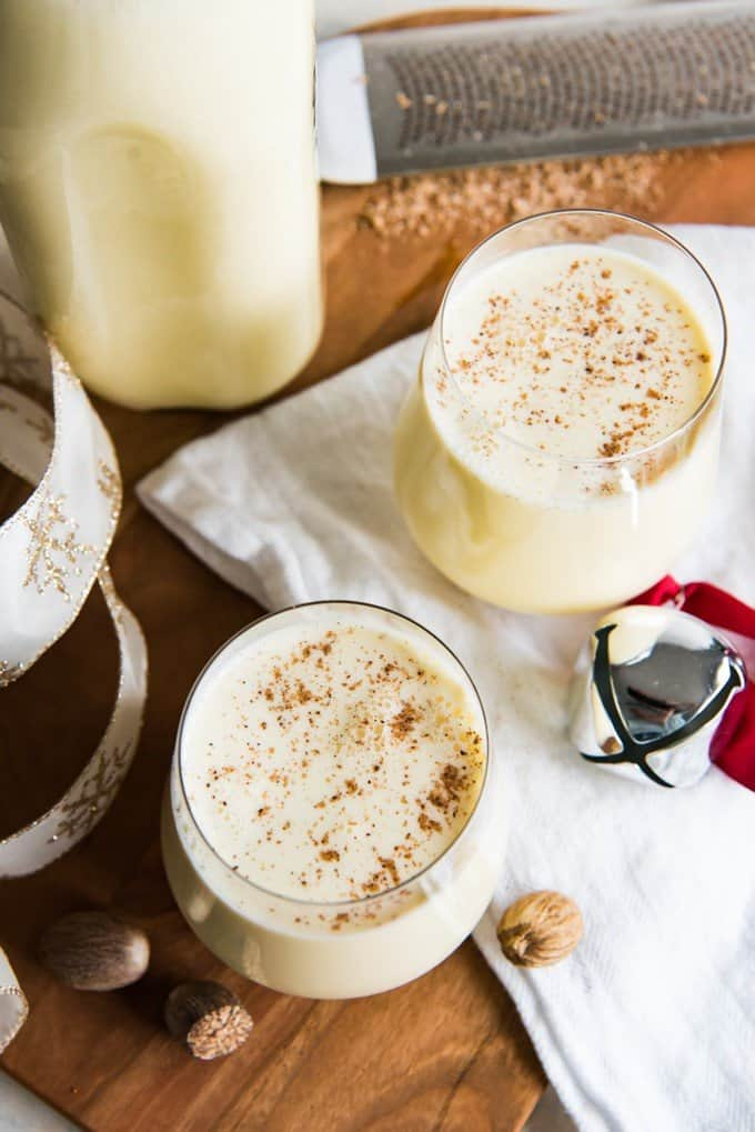 Aerial view of two glasses of nutmeg topped with grated nutmeg with a bell white towel ribbon and bottle of eggnog also in the frame