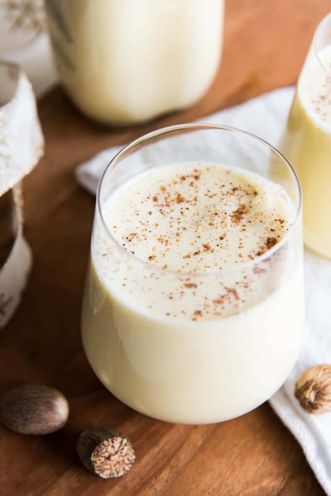 Glasses of eggnog topped with nutmeg on or next to a white towel with nuts ribbon and a bottle of eggnog around them