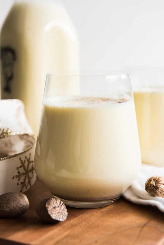An upclose side view of homemade eggnog topped with nutmeg in a glass with nuts, ribbon, another glass of eggnog and a bottle of eggnog around it