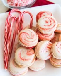 Peppermint Macarons on a white plate with whole candy canes and a bowl of crushed peppermint in back