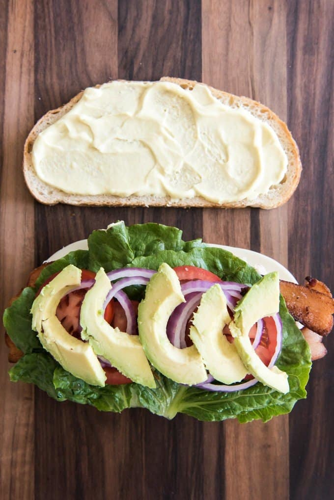 two slices of bread one with kneaders sauce on it and the other with baacon lettuce red tomato red onion and sliced avocados on it