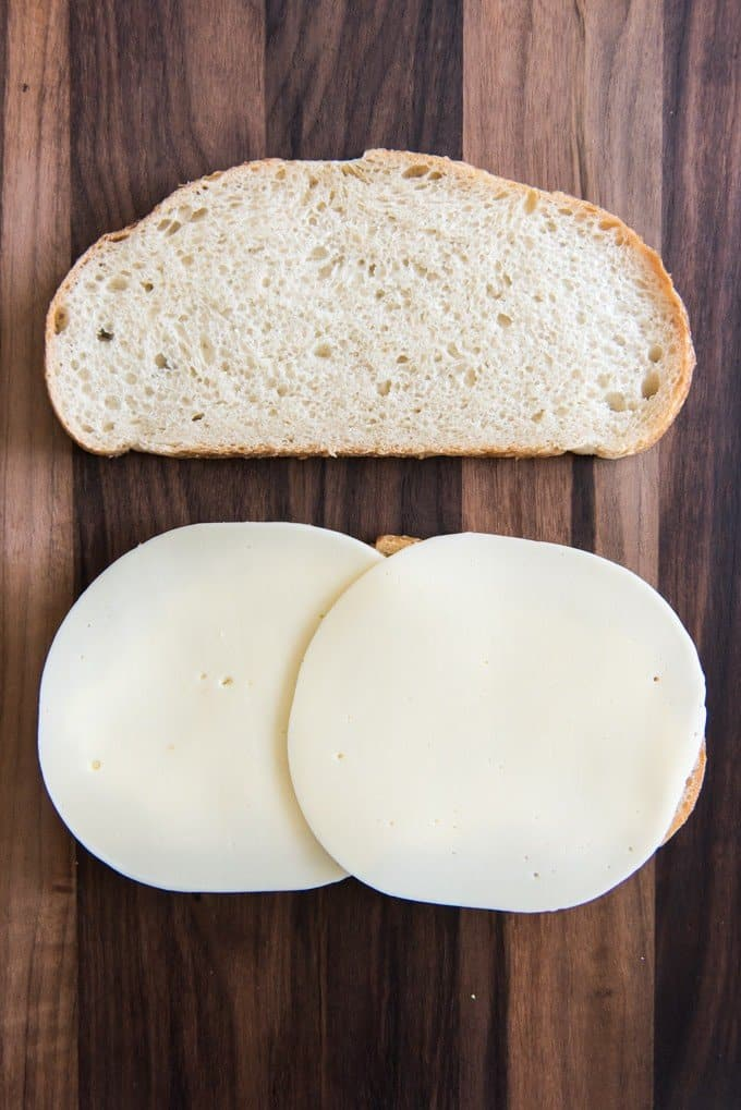 two slices of bread one with two slices of provolone cheese on it