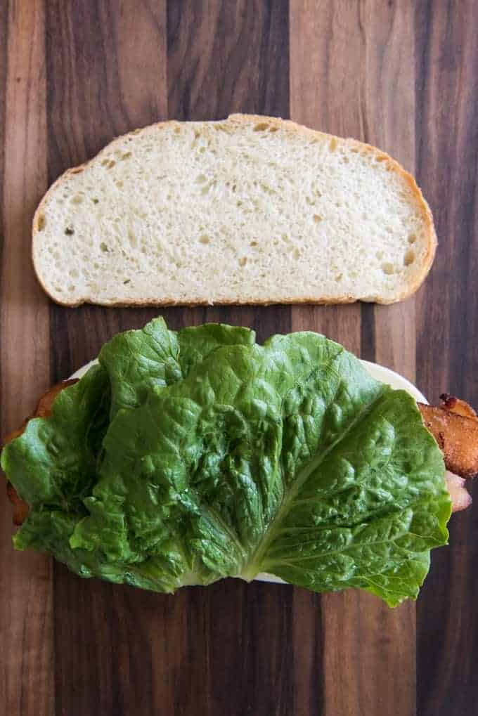 two slices of bread one with cheese bacon and lettuce on it