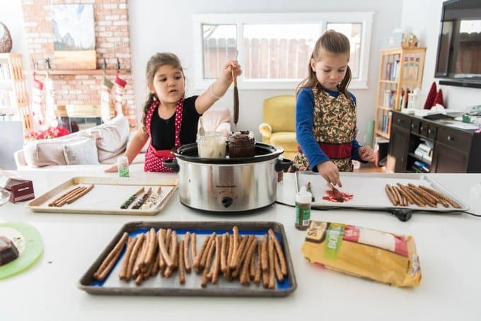 Dipping pretzel rods in chocolate melted in a slow cooker for a fun Christmas treat that's perfect for the kids to make!