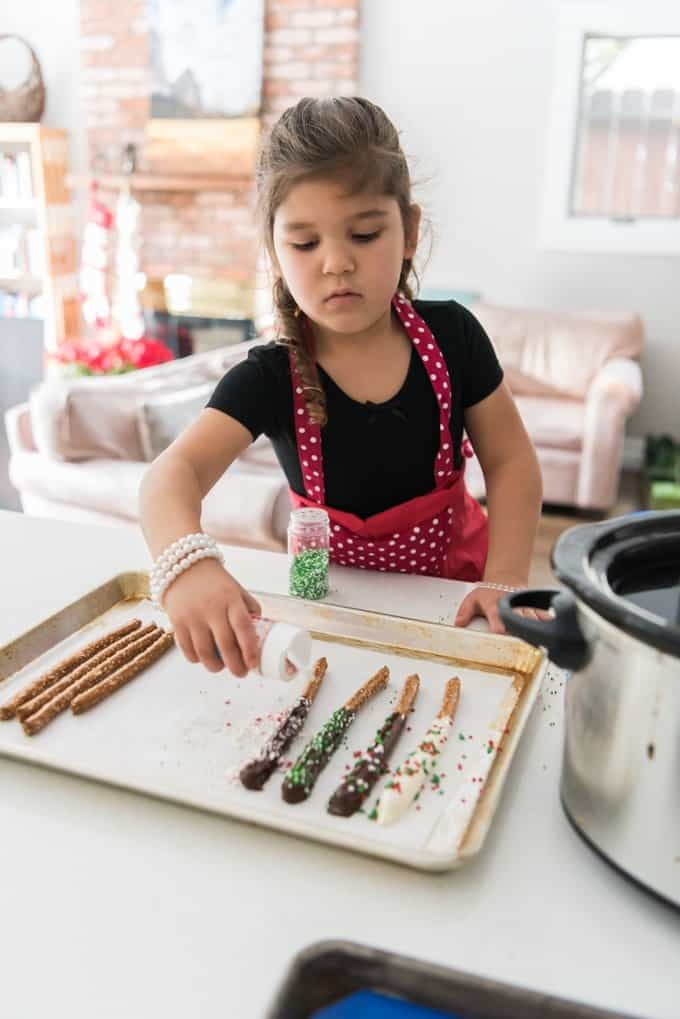 Adding sprinkles to chocolate covered pretzel rods.