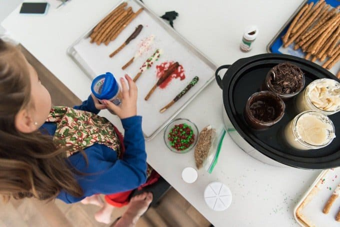 slow cooker with chocolate in mason jars and girl decorating chocolate covered pretzels