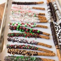 a parchment lined baking sheet with chocolate coated pretzelrods covered in sprinkles and other goodies
