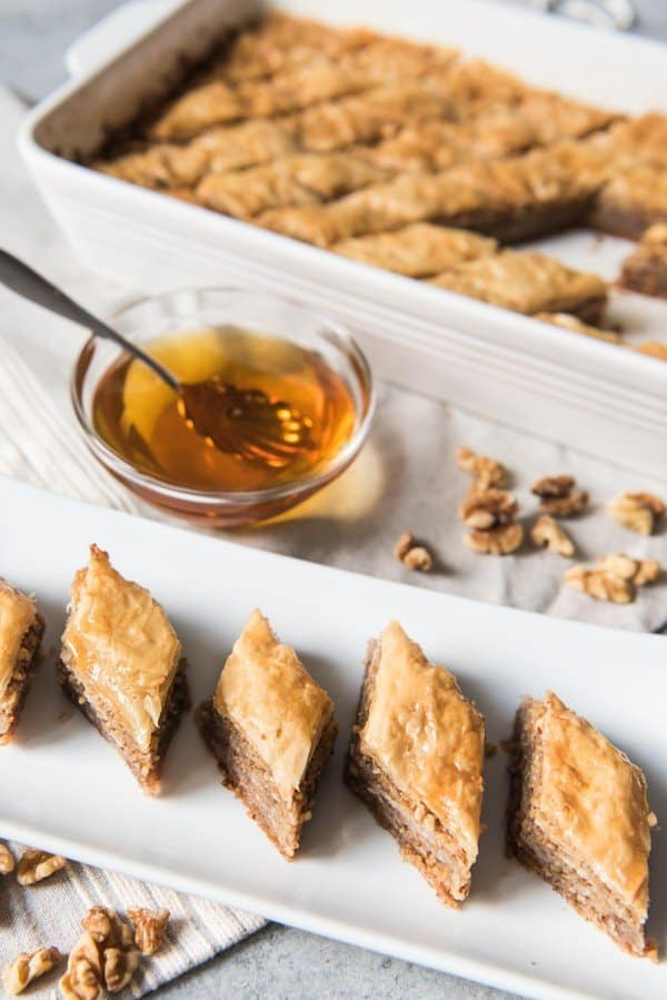 baklava slices on plate bowl of liquid with spoon and more baklava in a baking dish in back