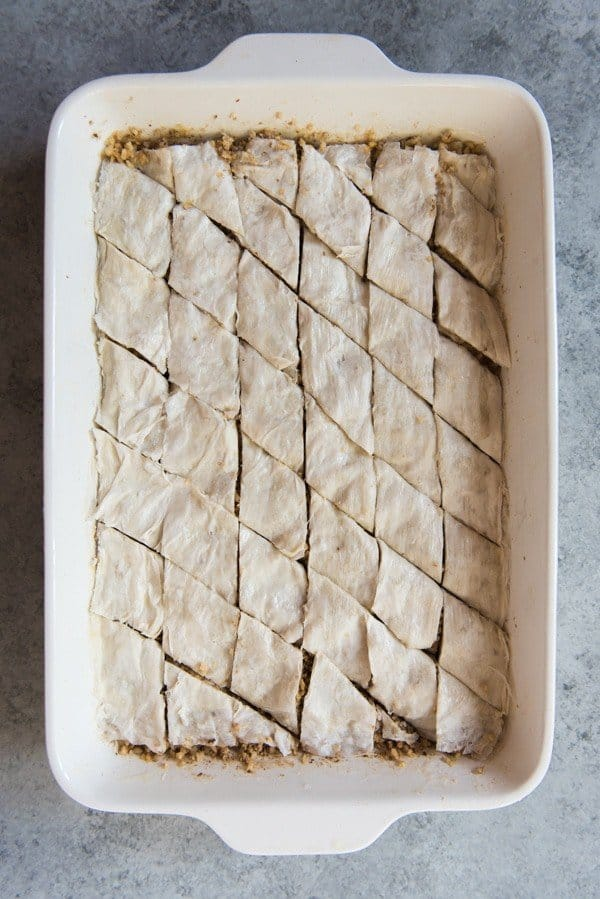 Unbaked baklava in a white baking dish cut into diamond