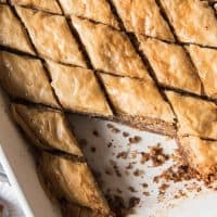 Greek Baklava in a baking dish cut into diamond shapes and a few pieces removed