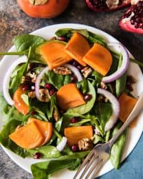 This festive Persimmon, Pomegranate, and Spinach Salad with a Maple Citrus Vinaigrette is easy to make and perfect for holiday dinners, using fresh produce available from late fall through winter.