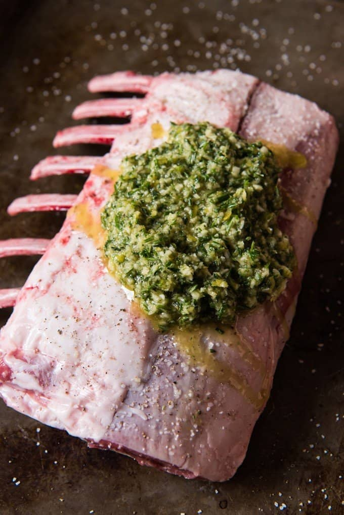 Rack of lamb fat side up with a marinade of olive oil, lemon zest, garlic, rosemary and thyme ready to be rubbed on it.