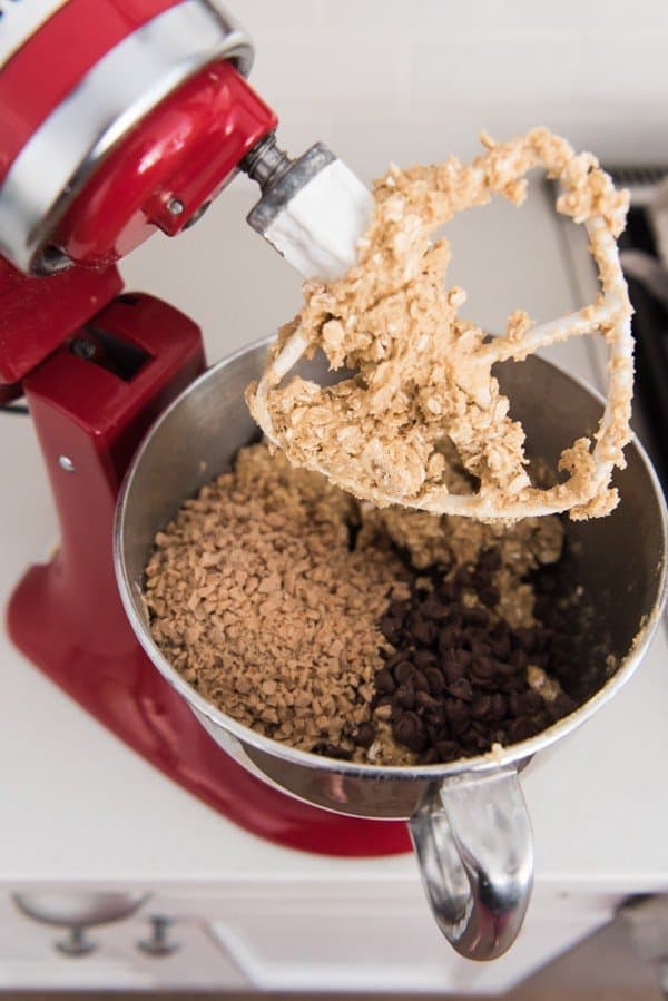 Red KitchenAid stand mixer with oatmeal cookie dough, toffee bits and milk chocolate chips ready to be mixed in.